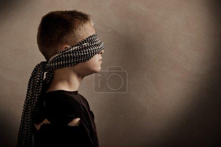 Photo pour Vue de profil côté garçon sérieux les yeux bandés avec espace copie devant lui pour concept tout enlèvement ou prise d'otage - image libre de droit