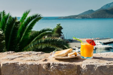 Breakfast of orange juice and toast with sea views.