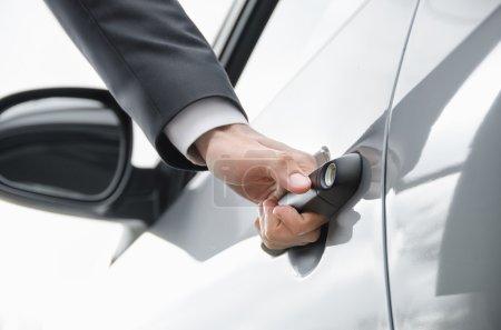 Photo pour Poignée à la main. Gros plan d'un homme d'affaires ouvrant une porte de voiture . - image libre de droit