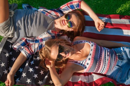 Young happy patriot women on the united states flag