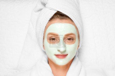 Beauty Treatments. Woman applying facial mask at spa