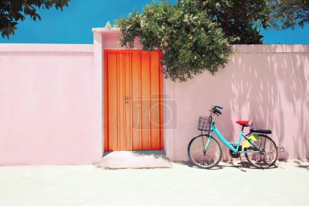 Blue bike near pink facade wall with orange door under blue sky