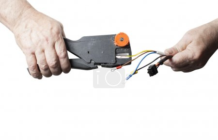 Repair, renovation, electricity and energy concept. Electrician peeling off insulation from wires isolated on white background. Copy space for text. Close up of hands with pliers.