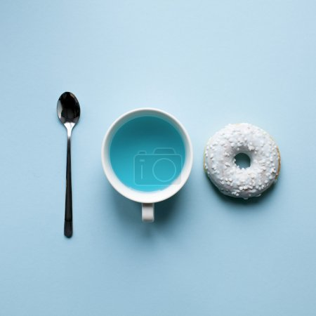 Photo for Donut, spoon and tea on blue background. Fine art poster - Royalty Free Image