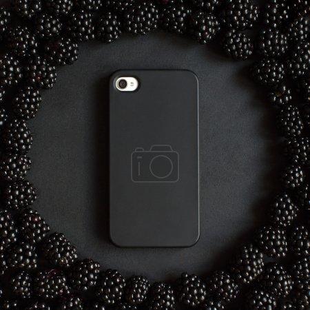 Photo pour Téléphone dans un boîtier noir sur fond de blackberry. Poster de téléphone noir design art - image libre de droit