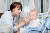 Mom feeds the baby at the table with a spoon. Healthy eating, fe