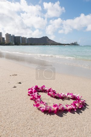 orchid flower garland necklace in love heart shape on white sea sand beach, romantic couple honeymoon trip at Hawaii .