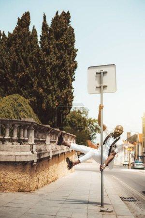 Photo pour Un homme noir barbu à la barbe chic dans des lunettes et un élégant costume blanc est accroché sur un panneau de signalisation ; un entrepreneur africain à la mode est en train de s'amuser et a sauté et attrapé le poteau près de la route - image libre de droit
