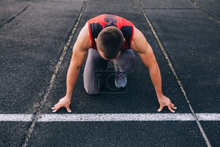 Photo for Sprinter leaving starting blocks on the running track - Royalty Free Image