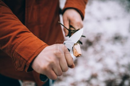 Photo for A man uses a knife to whittle a stick out hiking - Royalty Free Image