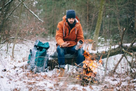 Traveller warming up by the fire in winter forest