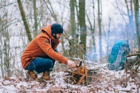 Photo pour Voyageurs réchauffés par le feu dans la forêt d'hiver. Veste rouge et sac à dos - image libre de droit