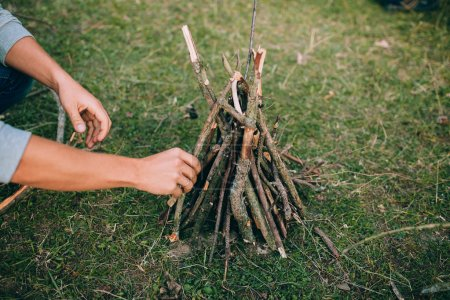 Photo for Man stacking dry sticks for campfire on green grass - Royalty Free Image