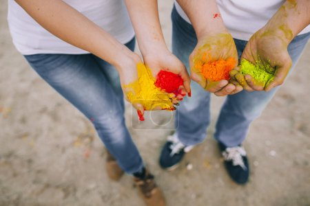 Couple holding handfuls of powdered paint...
