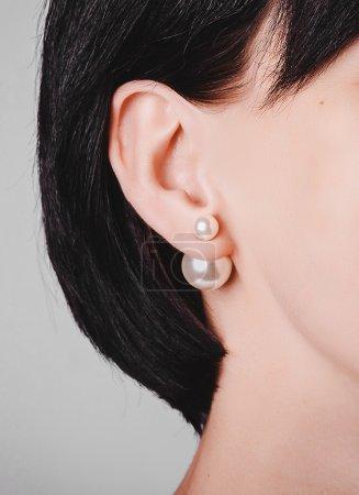 Photo pour Boucles d'oreilles or avec perles de cristal dans l'oreille de la femme - image libre de droit