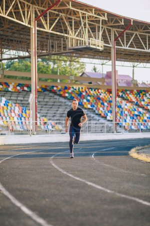 Photo for Male Runner on the track at a sport stadium - Royalty Free Image