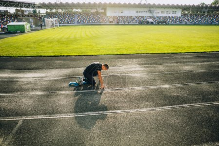 Photo for Sprinter leaving starting blocks on the running track. Explosive start. - Royalty Free Image