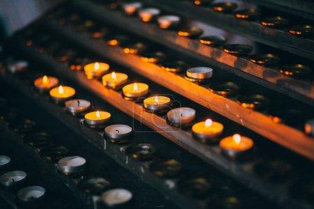Photo pour Bougies allumées disposées en lignes dans l'église - image libre de droit