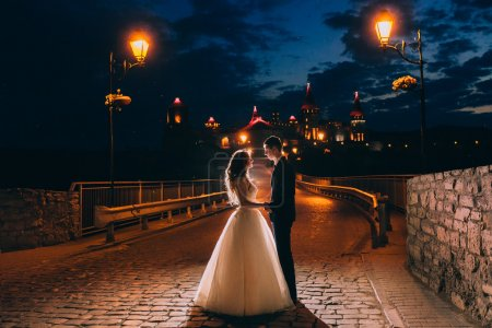 Photo pour Beau jeune couple embrasser dans la ville du soir - image libre de droit