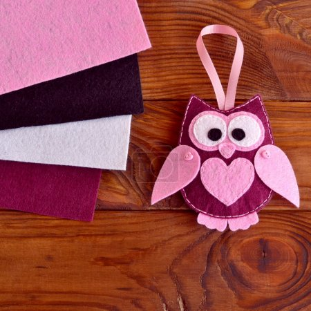 Funny maroon felt owl with a pink heart.