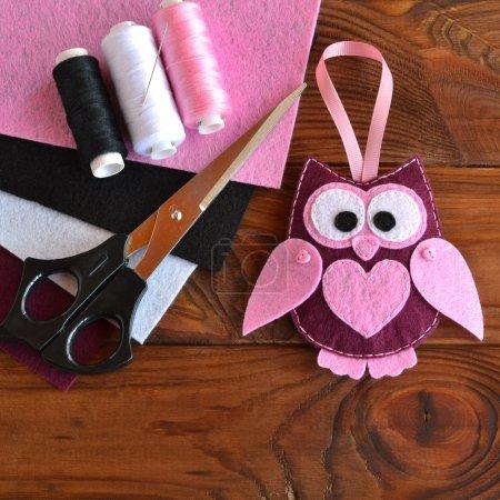 Felt owl toy. Kids DIY crafts. Sheets of colored felt, scissors, thread, needle, wooden table