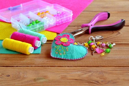 Beautiful keychain felt heart with colorful beads and flower. Box of beads, tools, sewing set, felt sheets on a wooden table. Children fabric project
