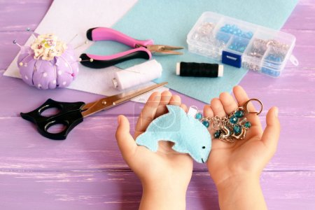 Child holds a felt dolphin toy in his hands. Home blue felt keychain with beads. Pincushion, thread, needles, pins, scissors, pliers, felt sheets, box of beads