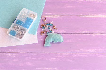 Hand cute felt dolphin keychain. Handbag charms. Handmade car keyring. Set of beads in a plastic box, felt sheets on lilac wooden background with free place for text. Summer crafts for kids concept