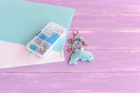 Handmade felt dolphin with beads. Cute keychain for bag charm. Summer children art idea. Beads kit in a plastic box, blue and white felt sheets on wooden table with empty place. Kids sewing background