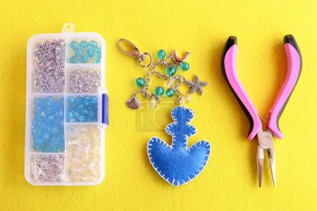 Blue felt anchor key chain with beads and metal pendants. Home made charm keychain for beach bags, scissors, pliers, box with different materials on yellow flat piece of felt. Sewing hobby background