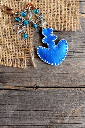 Anchor charm keychain for beach bag or car. Blue felt ornament with beads on old wooden background. Crafts idea for children, women, beginners. Top view