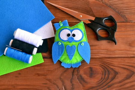 Felt owl embellishment. How to make a cute felt owl toy - kids crafts tutorial. Sheets of colored felt, scissors, thread, needle, wooden table
