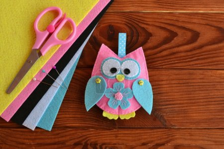 Felt owl embellishment. Felt owl toy. How to make a pretty felt owl. Kids DIY crafts tutorial. Sheets of colored felt, scissors, wooden table
