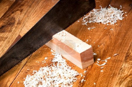 Sawing a board with a hand wood saw