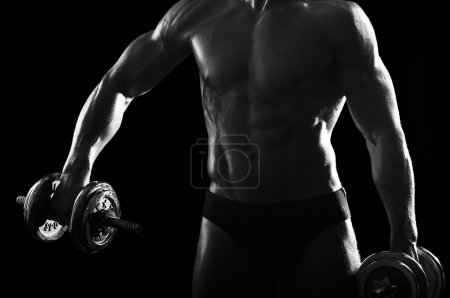 Part of muscular male body and large dumbbells.