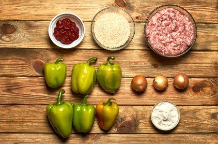 Foto de Pimienta, carne, arroz, tomate, sal, cebolla en una tabla de cocina. El proceso de preparación de los platos principales - Imagen libre de derechos
