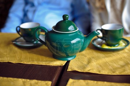 Green teapot and two cups of tea