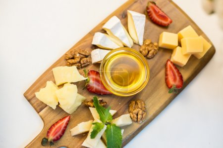 Cheese plate with nuts and strawberries