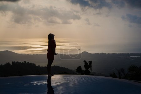 Silhouette of a woman on the panoramic swimming pool at sunset