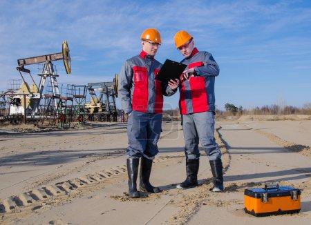 Photo pour Travailleurs dans le champ pétrolifère, un tenant la radio dans sa main. Pompage et fond de tête de puits. Boîte à outils au premier plan. Concept de pétrole et de gaz . - image libre de droit
