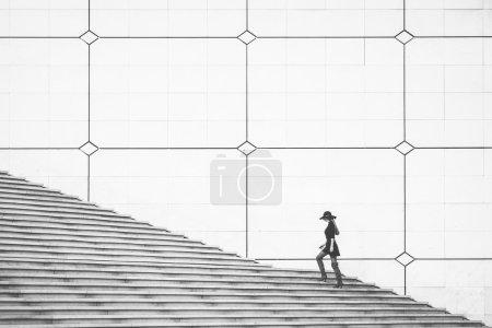 Photo pour Une femme marchant vers le haut de l'escalier, scène urbaine - image libre de droit