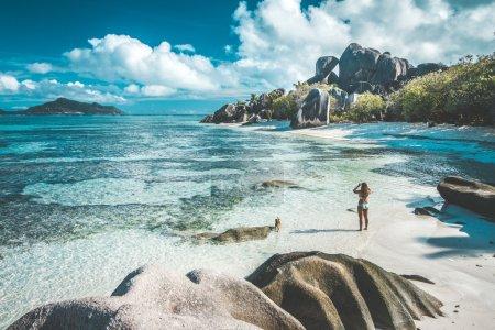 Photo pour Une femme de prendre des photos de la plus belle plage des Seychelles - Anse Source d'argent - image libre de droit