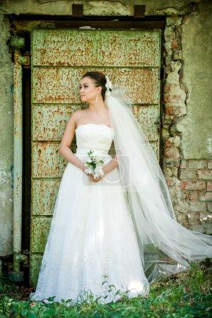 beautiful girl in wedding dress near old door