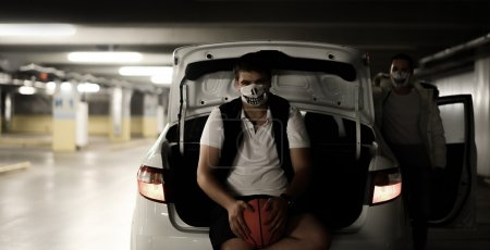 portrait of two men in the parking lot next to the car with a basketball in masks