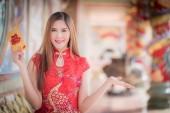 Číňanka šaty tradiční cheongsam a držet červené obálek