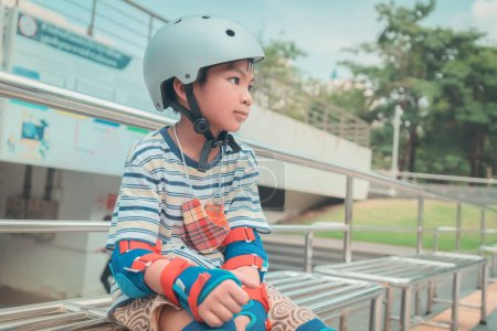 Photo for Asian Boy Skater wearing full protection gear is resting on side bench after long session in skating park. - Royalty Free Image