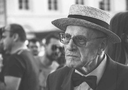 An unidentified old man in a straw hat and glasses