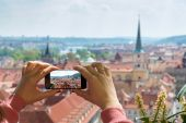 woman taking picture of Old Town in Prague with a smartphon