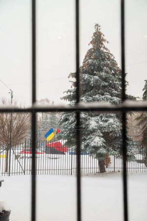 Iron window grill. On the street, the Ukrainian flag flies as a symbol of struggle and freedom