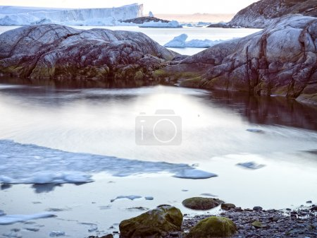 Long exposure shot with icebergs on the arctic ocean in the ilulissat icefjord, Greenland